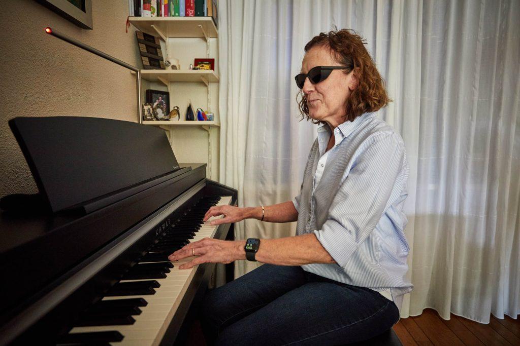Erna Fransen draagt een kappenbril tegen extreme fotofobie en speelt piano