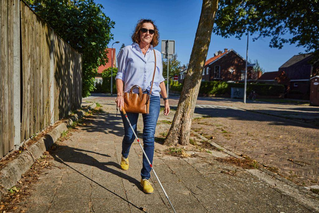 Erna Fransen draagt haar speciaal op maat gemaakte kappenbril tegen extreme fotofobie en wandelt buiten met een taststok.